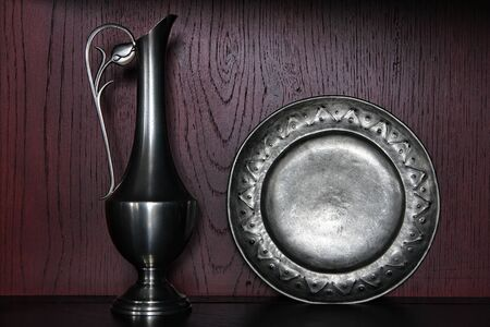 pewter: Antique silver serving pitcher and old colonial pewter plate on an aged cabinet shelf in a historic home