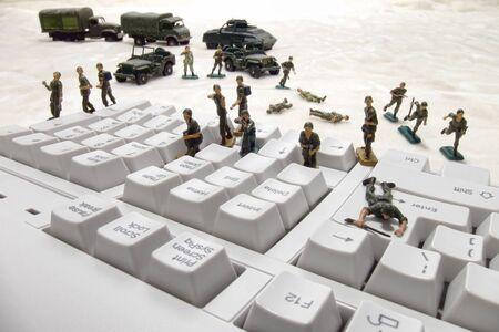 인터넷이나 네트워크 보안 바이러스 및 웜 감염의 위험에 대한 은유로 컴퓨터 키보드에 대한 공격 미니어처 육군 장난감 군인의 힘을 침입