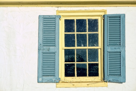 Old antique window with leaded glass panes and vintage wood shutters on a historic home colonial building