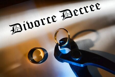 severance: Divorce decree final legal judgment document with pliers cutting a gold wedding ring in dramatic light Stock Photo