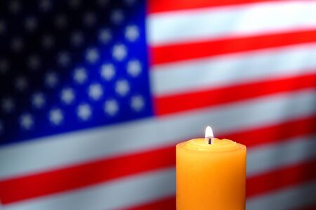 prayer candles: Commemorative prayer candle burning with a soft glowing flame in front of an American US flag