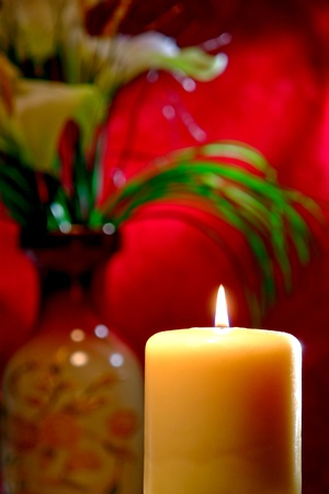 cor: Aromatherapy pillar candle burning with a soft glow flame in an Asian inspired d�cor