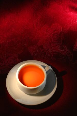 Cup of hot tea on a red damask placemat in a traditional Asian setting