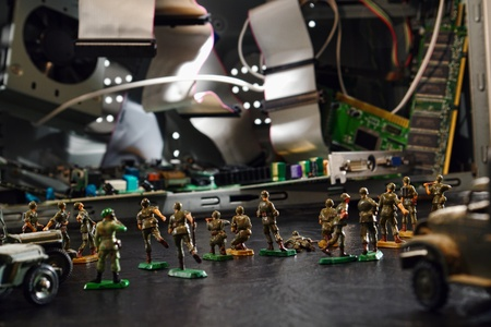 Army of miniature toy soldiers storming a computer illustrating how a coordinated cyber attack can wreck havoc on system hardware photo