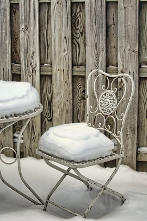 Decorative white metal garden chair and table covered with snow in a winter yard