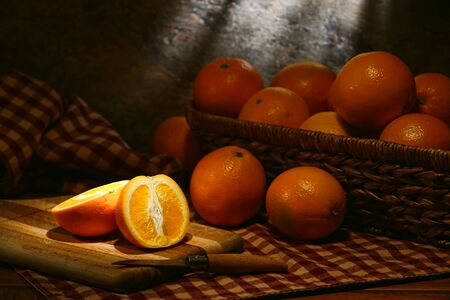 navel orange: Half cut orange fruit and Navel oranges in a rustic wicker basket on an old fashioned country table