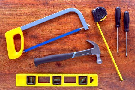 レベル、鋸、ハンマー、ドライバー、木製ワークベンチに巻尺と DIY の便利屋ツール コレクション