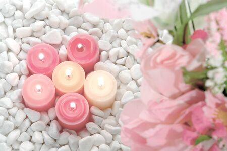 votive: Pastel tone votive candles burning over a bed of white pebbles with soft pink flower foreground Stock Photo