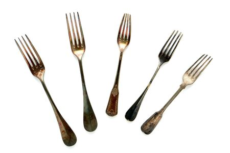 tarnished: Antique old and tarnished historic meat and salad silver fork collection on white Stock Photo