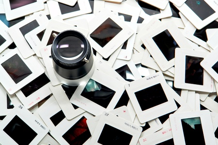 image editing: Photo editing magnifier loupe over stack of old transparency film slides in cardboard mount for a quality inspection (copyright holder and author is photographer)