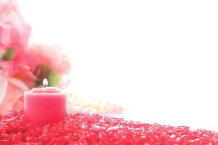 votive candle: Decorative pink votive candle burning with a soft glowing flame on a bed of pastel red crystals over white Stock Photo