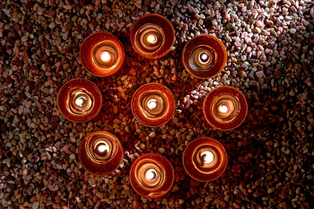votive: Symbolic meditation circle of votive candles burning with a soft glow flame over a bed of pea gravel in a spiritual retreat temple  Stock Photo