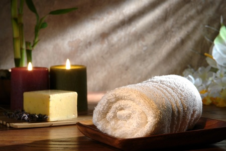 Soft white cotton towel in wood dish with candles burning for a pampering relaxation treatment in a spa Reklamní fotografie
