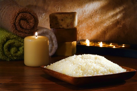 Natural bath sea salts in a wood bowl with cotton towels and artisan handmade soap bars gently lit by aromatherapy candles burning with a soft glow flame in a spa