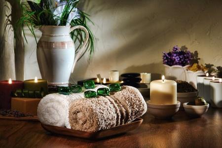 mimos: Cristal verde gemas de toallas de algodón blanco y marrón suave en un plato de madera con velas quemando y aromaterapia accesorios de tratamiento para una sesión de relajación mimos en un spa holístico