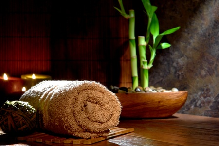 ambiance: Soft cotton brown hand towel with bamboo plant in a wood dish and candles in an Asian inspired spa