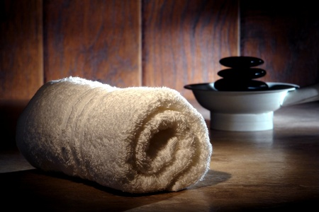 Soft white cotton towel and black polished hot massage stones cairn on a heater for a pampering relaxation treatment in a spa