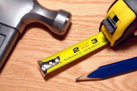 引き込み式の巻尺と爪ハンマーで木の板に大工道具