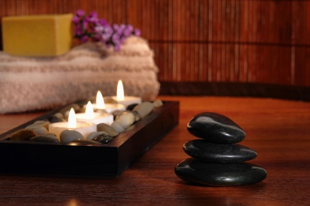 Polished black massage stone kern with Zen aromatherapy candles and towel in a spa