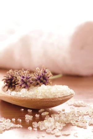 Natural sea bath salts in a wood spoon with fresh cut lavender flowers in a spa