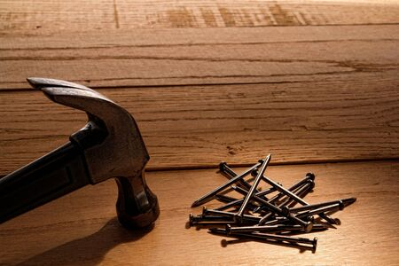 Pile of common nails and carpenter claw hammer tool on wood boards in a construction workshop Stock Photo - 10287039