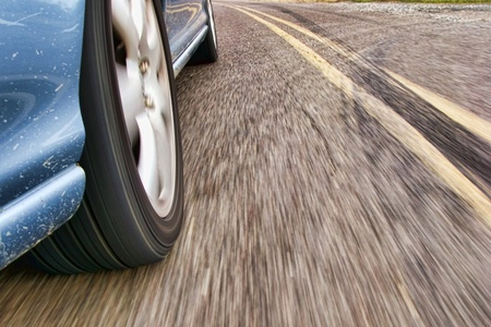 Fast car speeding on a country road with wheel and road motion blur