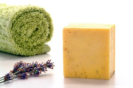 wisps: Block style bar of natural artisan aromatherapy soap with fresh lavender flower wisps and soft towel in a spa