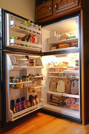 Top freezer refrigerator with doors open full of fresh food and bottles photo