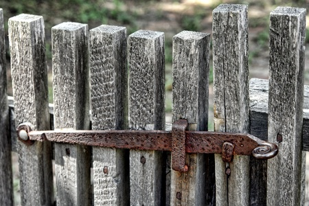 Old and rusty metal gate closing latch on a historic house garden gate photo