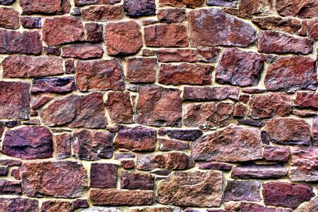 stone wall: Old house stone wall made of randomly stacked red blocks with mortar joints