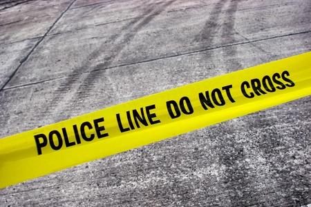escena del crimen: El crimen callejero con l�nea de polic�a no cruzan cinta de alerta amarilla por encima de la carretera con neum�ticos pistas Foto de archivo