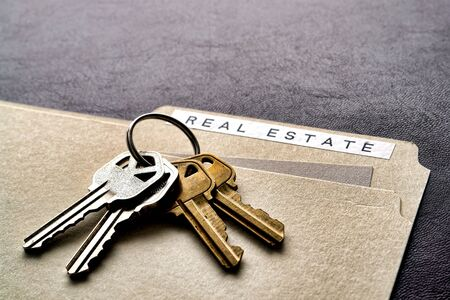 Ring set of house keys on a real estate file folder on a desk Stock Photo