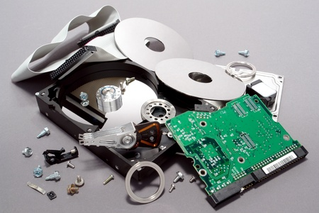 Seriously crashed and dismantled computer hard drive with scattered parts