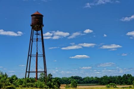 Oud en roestig verlaten industrieel water toren met reservoir tank op een Brownfield fabriek recovery site Stockfoto