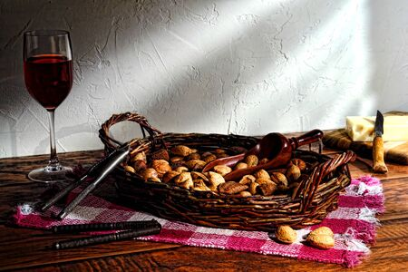 Assorted nuts in shell in a rustic wicker basket with nutcrackers for an old fashioned country meal photo