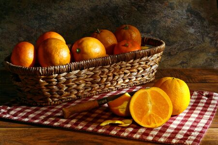 navel orange: Half cut orange and ripe oranges in a rustic wicker basket for an old fashioned country meal