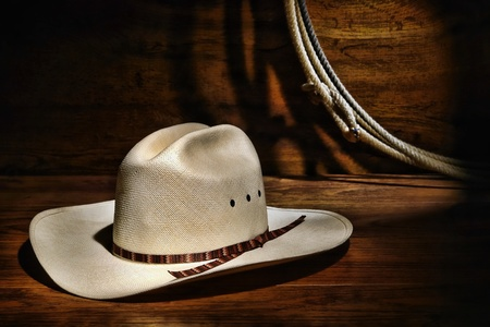 hondo: American West rodeo cowboy white straw hat and lasso rope on wood Stock Photo