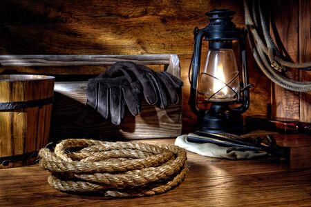 rodeo americano: American West vaquero de rodeo cría de cuerda e instrumentos de labranza en un granero Foto de archivo