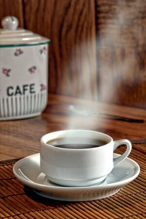 steaming coffee: Cup of steaming hot black coffee with vintage cafe porcelain jar in a coffe shop