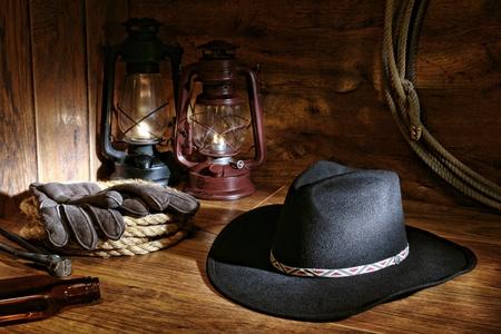 rodeo americano: Vaquero de rodeo oeste americano negro sintió sombrero y herramientas de ganadería en un granero