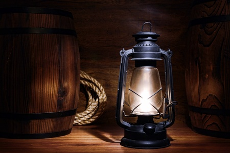 kerosene lamp: Old kerosene lantern burning with bright flame between wood barrels in a vintage country  barn warehouse  Stock Photo