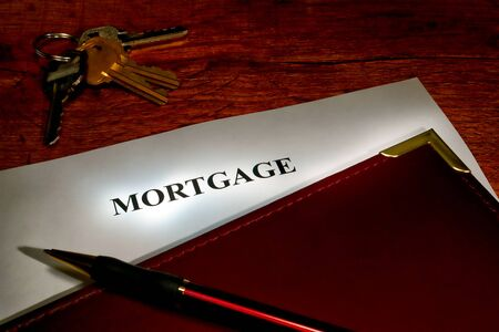Mortgage document in a leather binder with pen and set of house keys on a wood desk