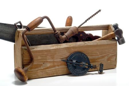 Antique work tools in an old vintage wood toolbox over white Reklamní fotografie