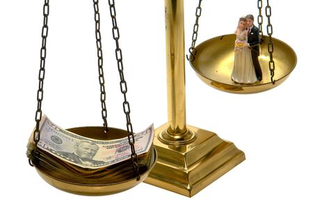 Balance scale with pile of cash and wedding couple figurine in pans over white photo