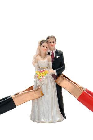 hooked: Jumper cables clamps hooked onto a married couple wedding figurine for a relationship jump start isolated on white  Stock Photo