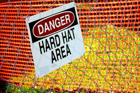 hard: Danger hard hat area safety warning sign on a chain link fence in a work site construction zone