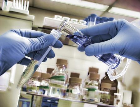 Wetenschapper handen die twee glazen wetenschappelijke cilinders gevuld met vloeistof voor een experiment in een wetenschappelijk onderzoek lab