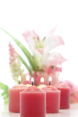 votive candle: Pink votive candles softly burning before a pastel floral arrangement over white background