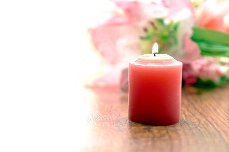 votive candle: Pink votive candle burning with a soft glow before a pastel color flower bouquet in background over white Stock Photo