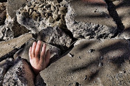 catastrophic: Dead man hand sticking out of demolished concrete rubble debris after a catastrophic disaster earthquake (fictitious staged photograph)